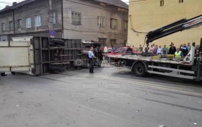 Un autocamion s-a răsturnat după ce a lovit un autoturism